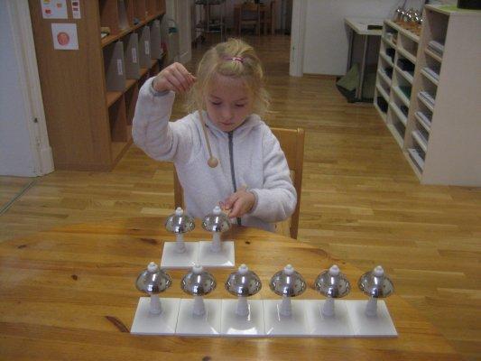 Arbeit mit Montessori-Glocken - Ziele: Wahrnehmung unterschiedlicher Tonhöhen, Entwicklung des musikalischen Gehörs und des musikalischen Gedächtnisses, Entwicklung der Stimme für das Singen, Vorbereitung auf die musikalische Erziehung, Vorbereitung auf das Schreiben und Lesen