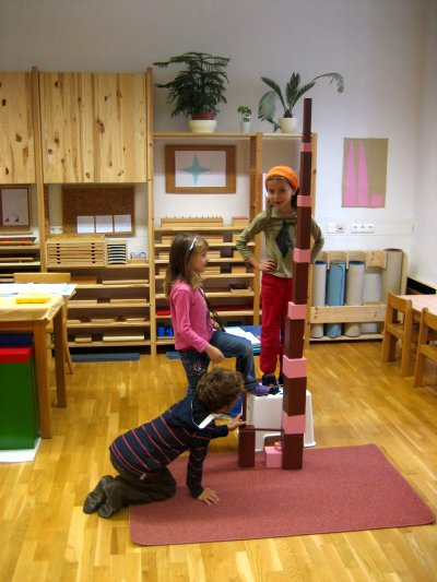 Geometrie - Rosa Turm und Braune Treppe - Ziele: Entwicklung der visuellen Wahrnehmung von allen drei Dimensionen über das Begreifen, Entwicklung der Groß- und Feinmotorik, Auge-Hand-Koordination, Entdecken und Aufbauen von Ordnungsstrukturen, Vorbereitung auf die Volumenberechnung